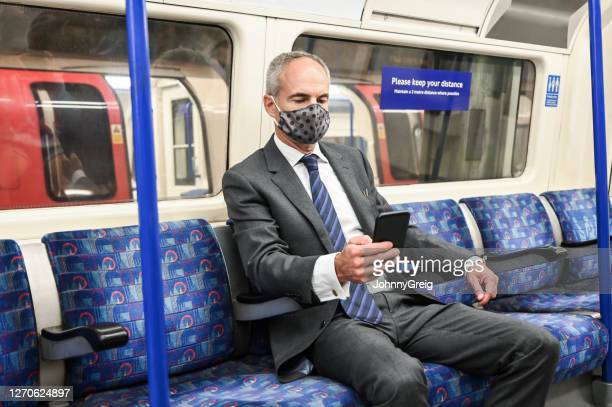 executive in early 50s wearing protective face mask on train - portable information device stock pictures, royalty-free photos & images