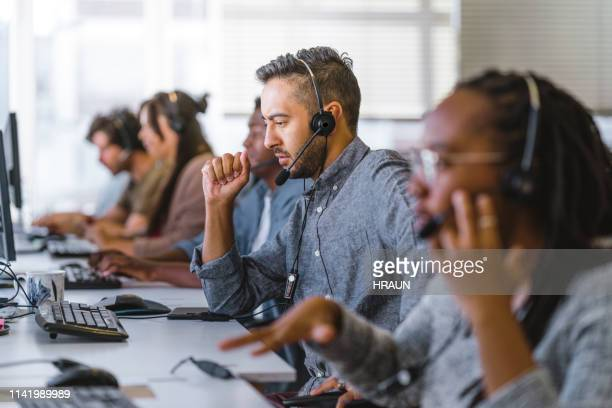 executive listening to customer query on headset - hands free device stock pictures, royalty-free photos & images