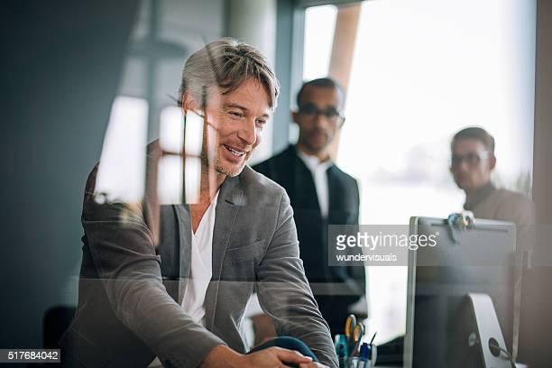 Executive-Mann sitzt in vor Glas schaut an Bildschirm