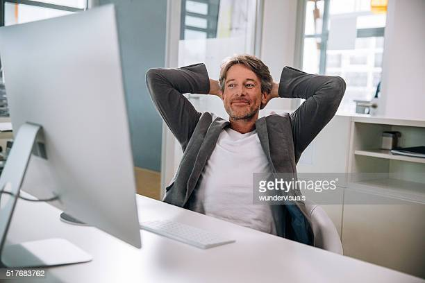 Executive mature man relaxing in office chair