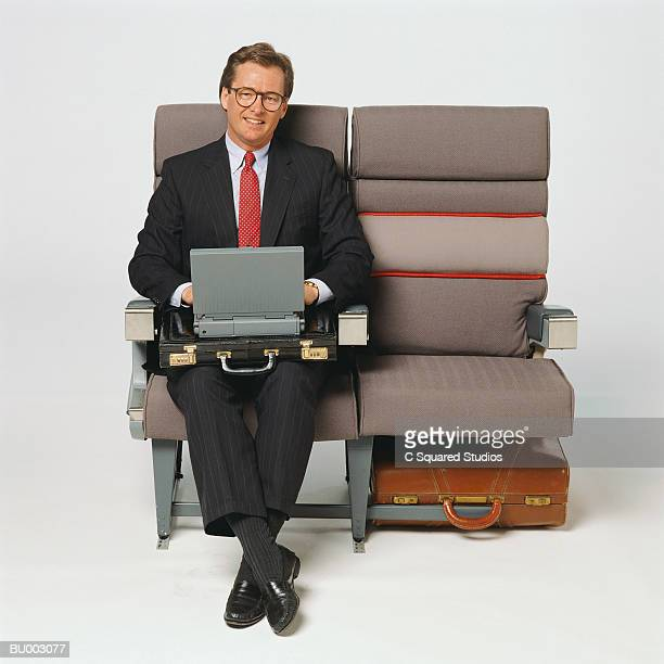 Executive on Airplane with Laptop