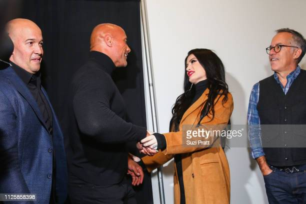 Executive producer Hiram Garcia walks by as actor and producer Dwayne Johnson greets Paige while Sundance Film Festival Director John Cooper looks on...