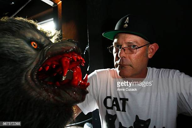 Executive producer of Halloween Horror Nights at Universal Studios Hollywood John Murdy poses with one of many werewolves during a tour of the mazes...