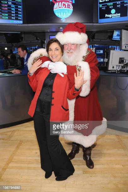 Executive Producer of Macy's Thanksgiving Day Parade Amy Kule and Santa Claus pose for pictures after ringing the opening bell at the New York Stock...