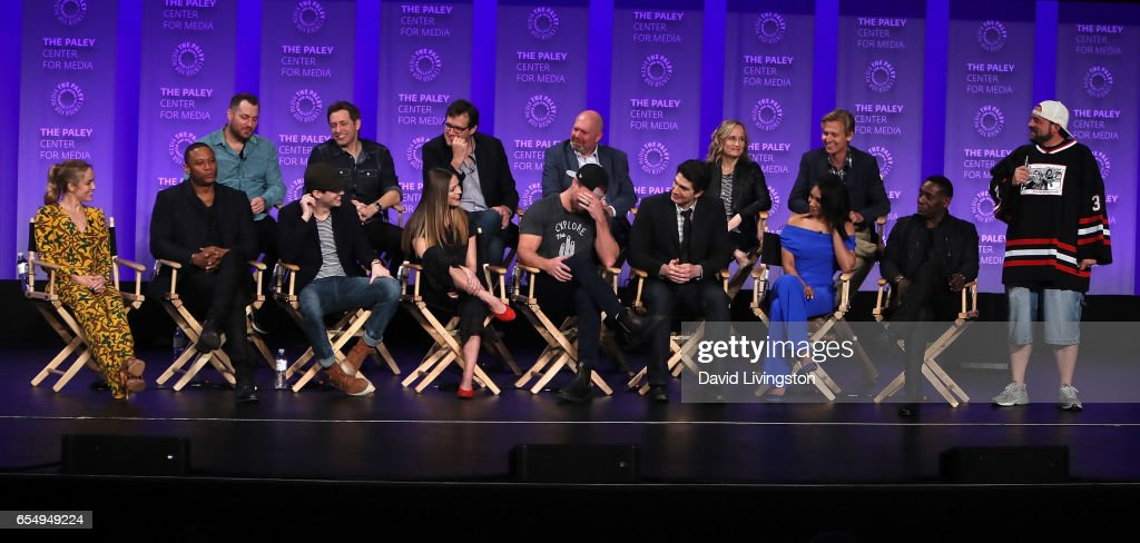 Executive producers Aaron Helbing, Todd Helbing, Andrew Kreisberg, Marc Guggenheim, Wendy Mericle and Phil Klemmer and (L-R, front row) actors Caity Lotz, David Ramsey, Grant Gustin, Melissa Benoist, Stephen Amell, Brandon Routh, Candice Patton and David Harewood and director/moderator Kevin Smith appear on stage at The Paley Center for Media's 34th Annual PaleyFest Los Angeles presentation of The CW's Heroes & Aliens at Dolby Theatre on March 18, 2017 in Hollywood, California.