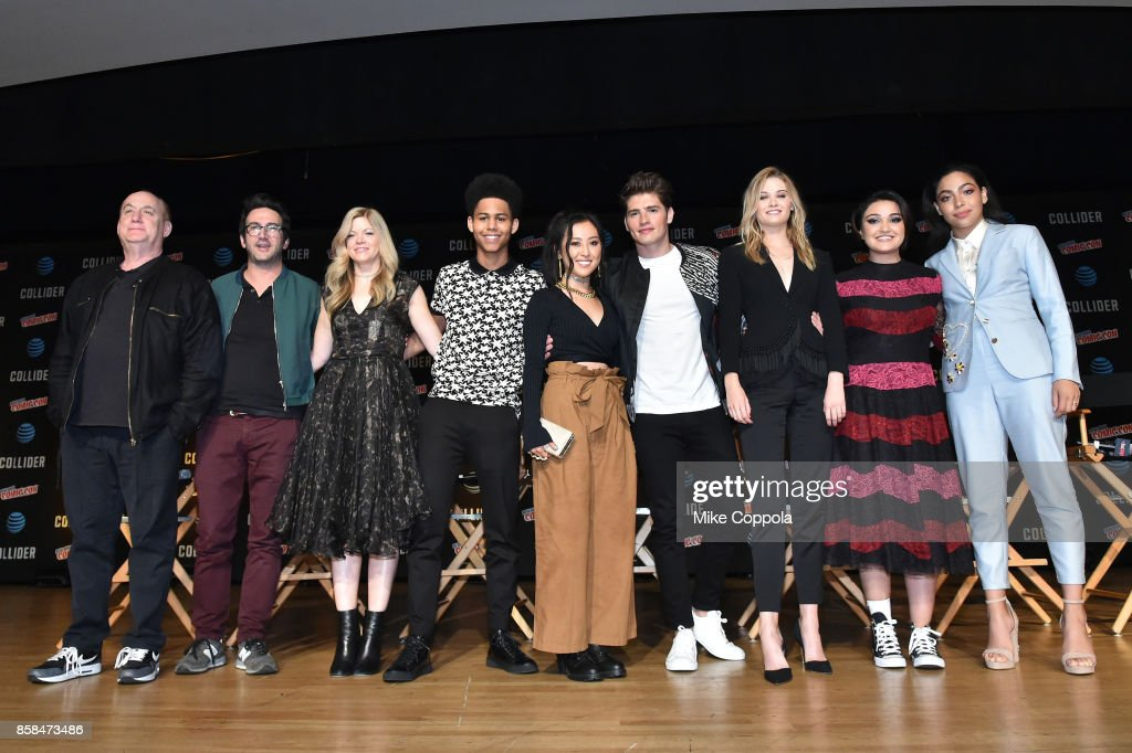 (L-R Executive producers Jeph Loeb, Josh Schwartz, and Stephanie Savage and actors Rhenzy Feliz, Lyrica Okano, Gregg Sulkin, Virginia Gardner, Ariela Barer, and Allegra Acosta pose onstage after Hulu's Runaways panel at New York Comic Con at Jacob Javits Center on October 6, 2017 in New York City.