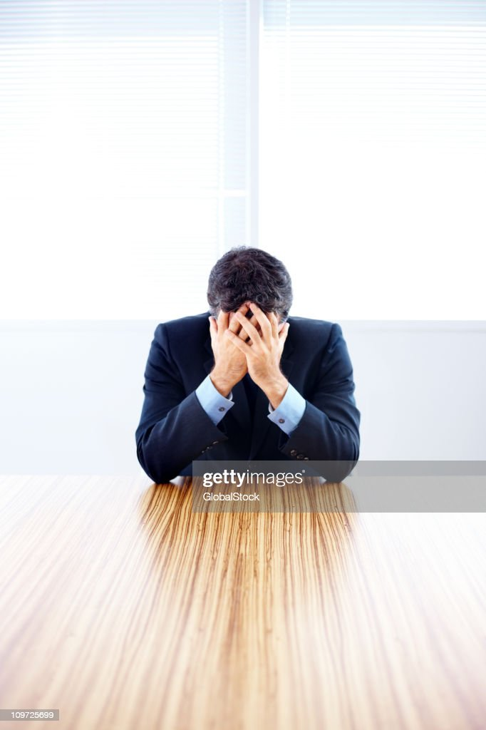 Executive sitting with head in hands at a conference room : Stockfoto