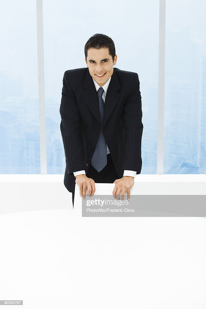 Executive standing behind chair, smiling at camera, portrait : Stock Photo