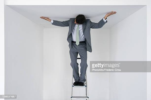 Executive standing on stepladder, arms outstretched on ceiling