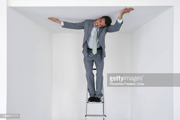 executive standing on stepladder, pushing ceiling - restraining stock photos and pictures
