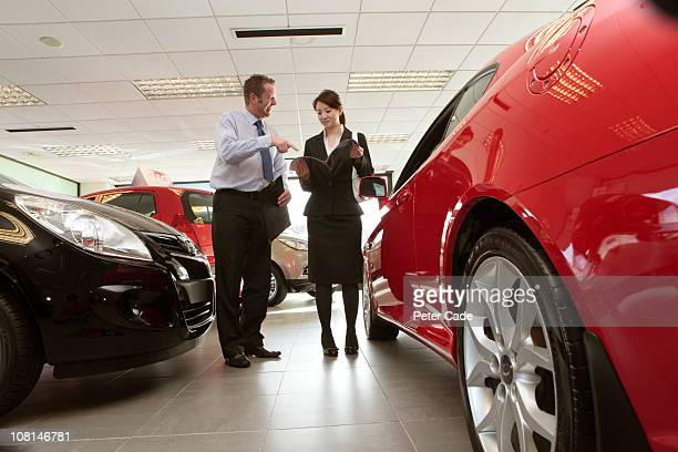 executive talking to salesman in car showroom - car salesperson stock pictures, royalty-free photos & images