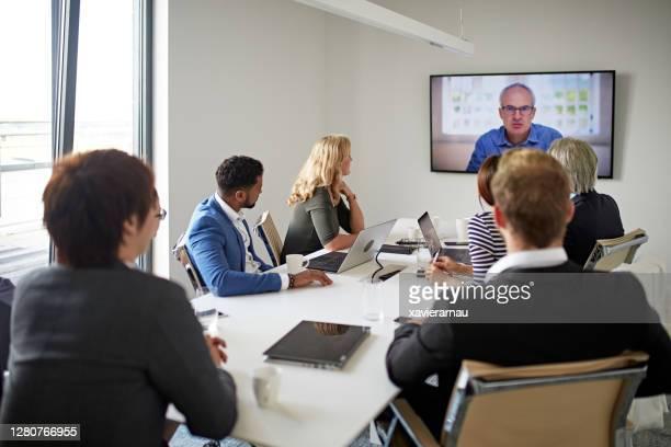 ビデオ会議でコミュニケーションを取るエグゼクティブチームとceo - 大型テレビ ストックフォトと画像