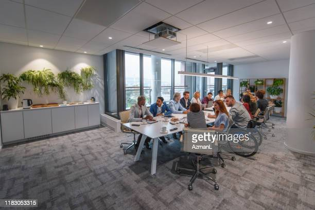 executive team sitting at conference table in board room - employee engagement stock pictures, royalty-free photos & images