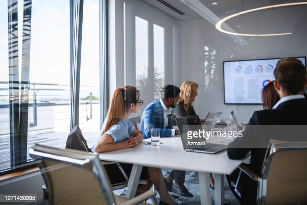 executive team watching video in office conference room - organised group stock pictures, royalty-free photos & images