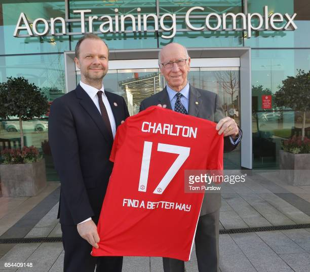 Executive Vice Chairman Ed Woodward and Sir Bobby Charlton of Manchester United pose with a shirt promoting Find A Better Way a charity set up by Sir...