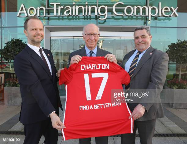 Executive Vice Chairman Ed Woodward and Sir Bobby Charlton of Manchester United pose with Lou McGrath OBE Chief Executive of Find A Better Way a...