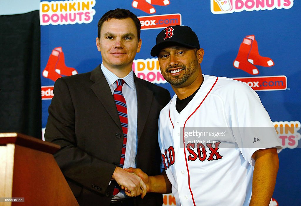 Executive Vice President and General Manager of the Boston Red Sox Ben Cherington (L) shakes hands with Shane Victorino, after signing him to a three-year contract, on December 13, 2012 at Fenway Park in Boston, Massachusetts.