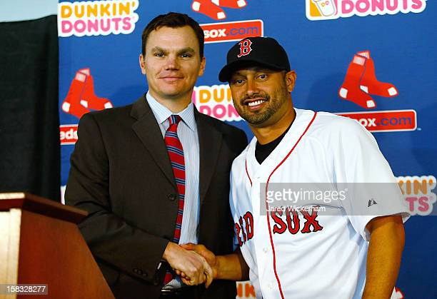Executive Vice President and General Manager of the Boston Red Sox Ben Cherington shakes hands with Shane Victorino after signing him to a threeyear...