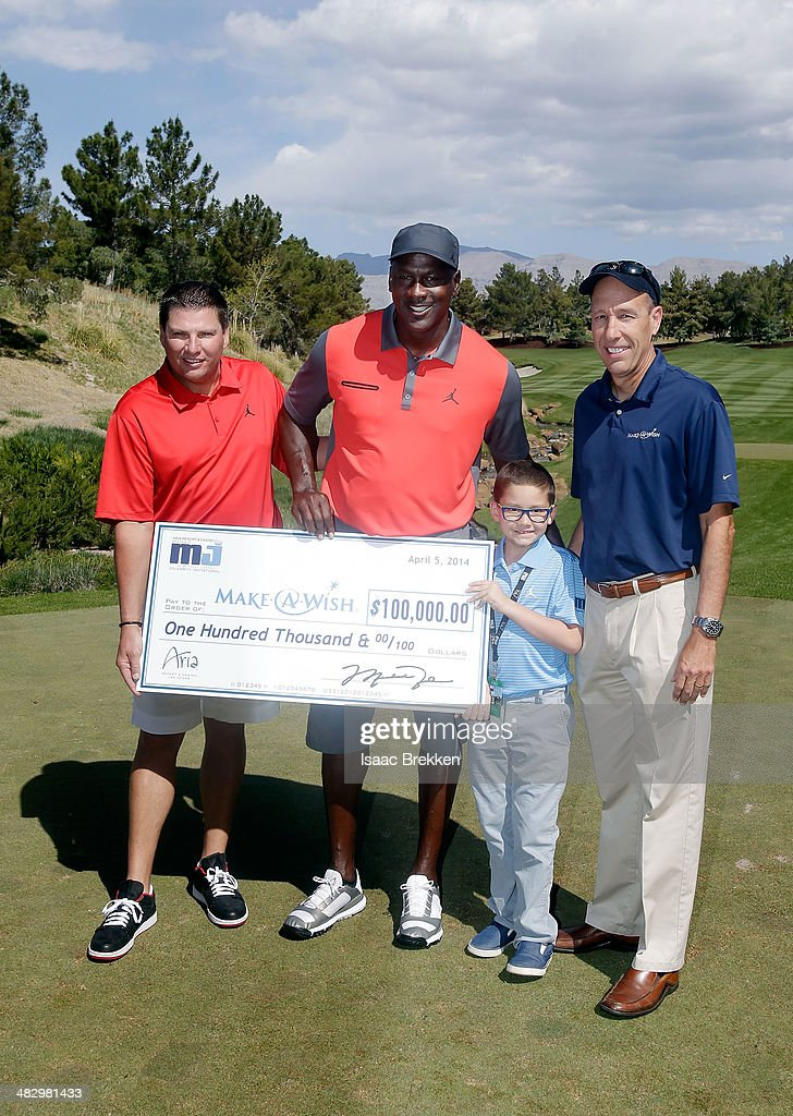 Executive Vice President MGM Resorts International Tyler Shook (L) and NBA legend Michael Jordan present a check to Make-A-Wish during Aria Resort & Casino's 13th Annual Michael Jordan Celebrity Invitational at Shadow Creek on April 5, 2014 in North Las Vegas, Nevada.