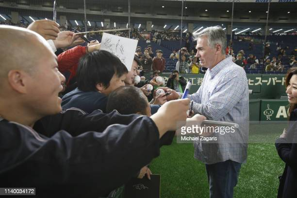 Executive Vice President of Baseball Operations Billy Beane of the Oakland Athletics signs autographs prior to the game between the Athletics and the...