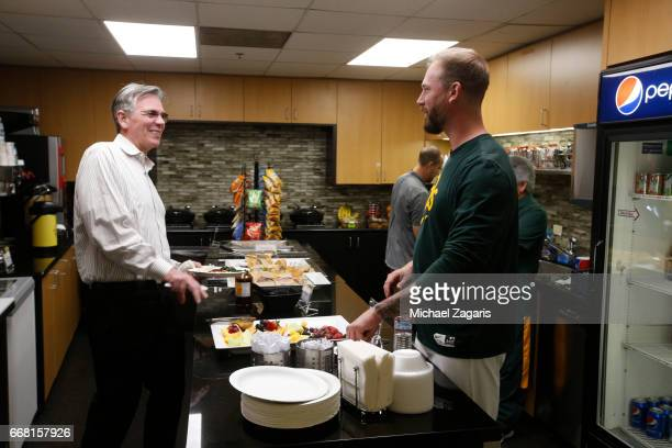 Executive Vice President of Baseball Operations Billy Beane of the Oakland Athletics talks with John Axford in the clubhouse prior to the game...