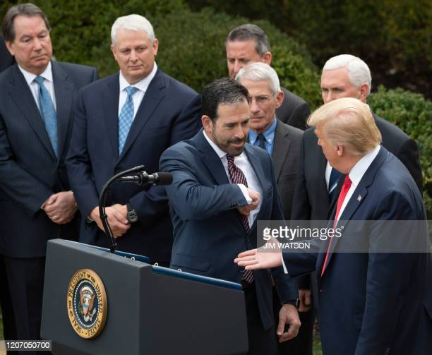 Executive VP and Chief Strategy Innovation Officer for LHC Group Inc Bruce Greenstein offers an elbow bump as US President Donald Trump reaches for a...