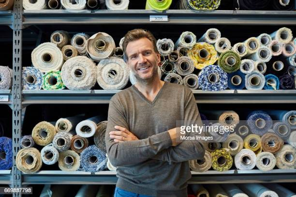 executive with arms crossed against rolled fabric - textile industry stock pictures, royalty-free photos & images