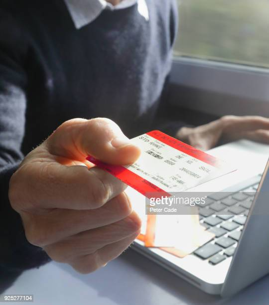 executive with laptop on train with ticket