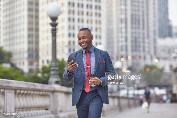 Executive with mobile phone and coffee cup in city