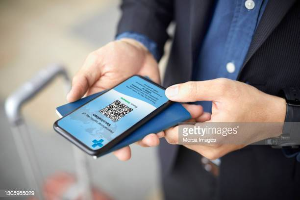 executive with online covid-19 vaccine passport on phone - airport stock pictures, royalty-free photos & images