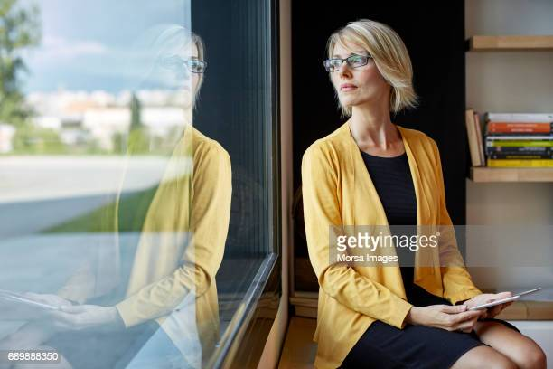 executive with tablet pc looking through window - riflesso foto e immagini stock