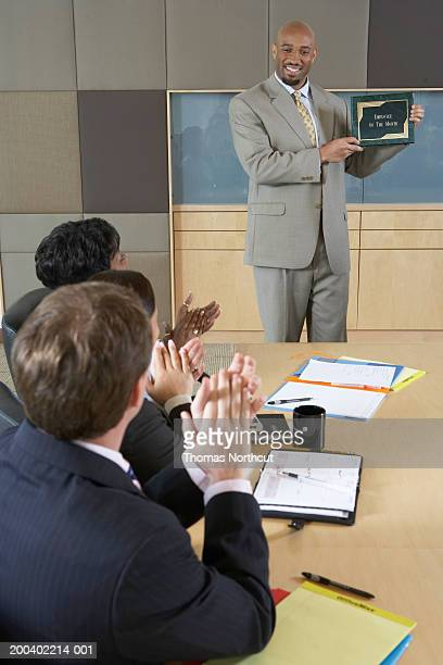 Executives applauding for man holding 'Employee of the Month' plaque