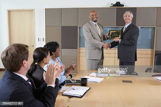 Executives applauding for man receiving 'Employee of the Month' plaque