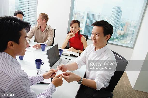 Executives around conference table, two businessmen exchanging business cards