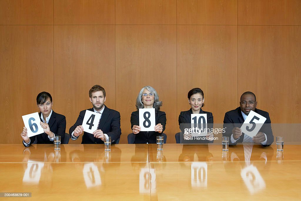 Executives at conference table holding score cards, portrait : Stock Photo