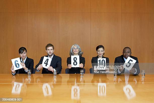 Executives at conference table holding score cards, portrait