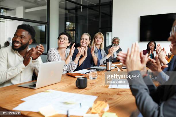 executives clapping by table in office meeting - applauding stock pictures, royalty-free photos & images