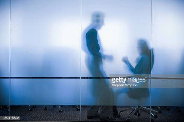 executives confer behind frosted glass