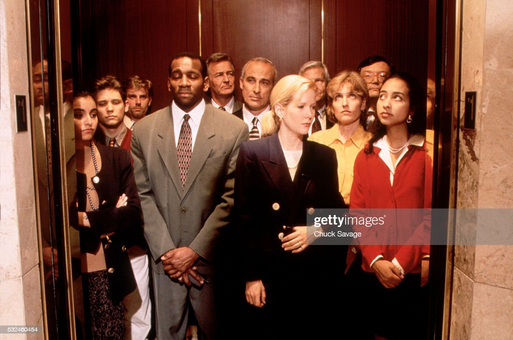 Executives crowded into elevator : Stock Photo