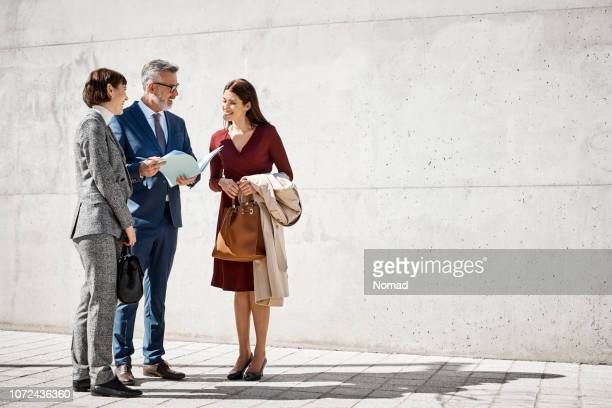 executives discussing over documents on street - three people stock pictures, royalty-free photos & images