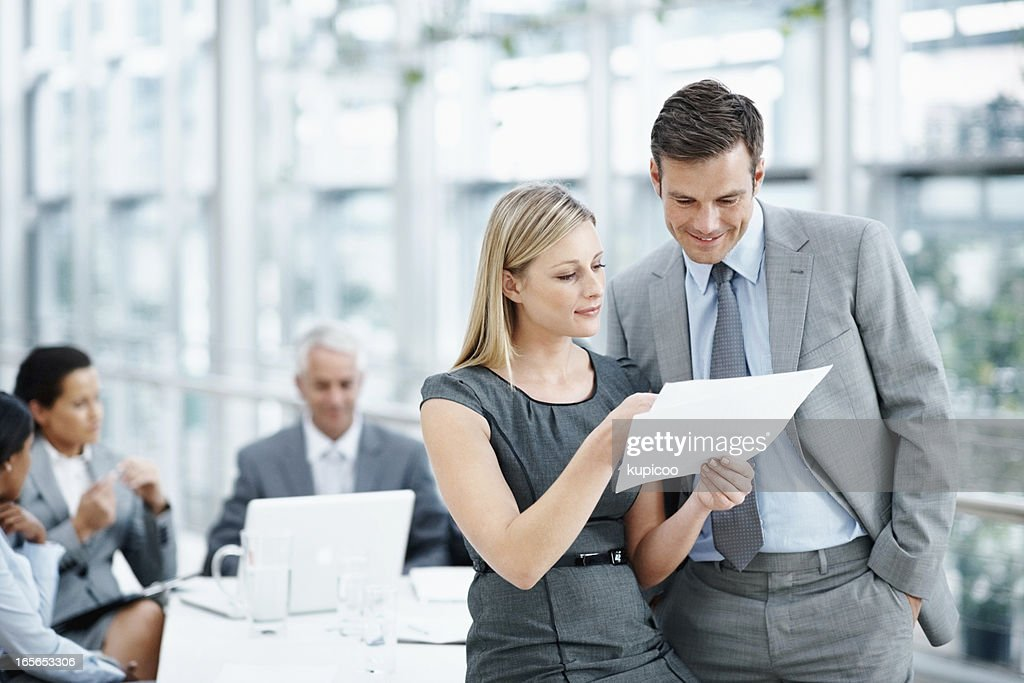 Executives going through a document with team in meeting : Stock Photo