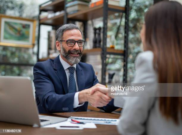 executives handshaking in a coffee shop - financial advisor stock pictures, royalty-free photos & images