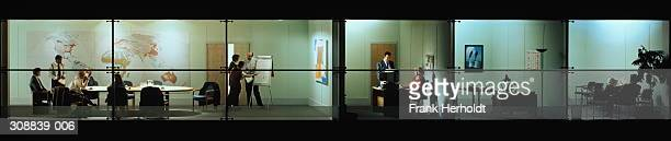 Executives in conference room at night, view through office windows