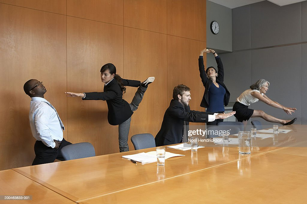 Executives in conference room stretching : Stock Photo