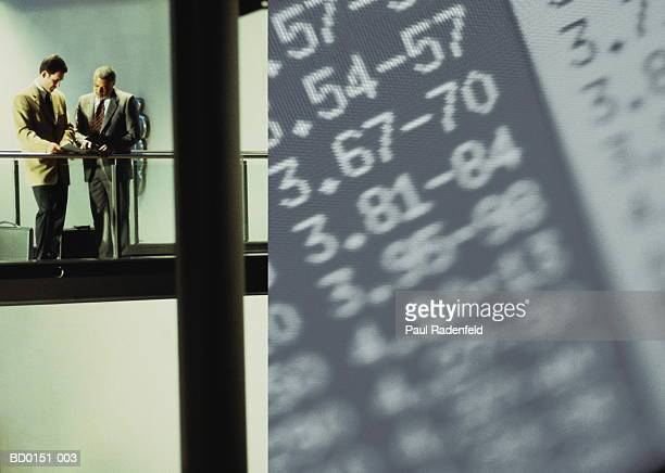 Executives in discussion on balcony with financial data (montage)