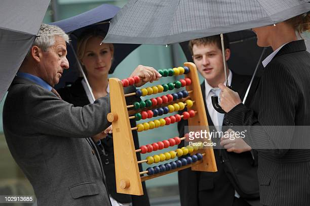 Executives looking at abacus