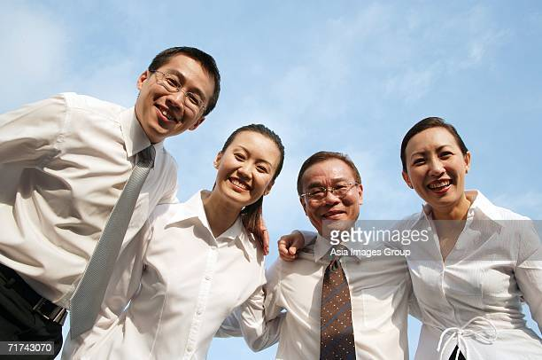 executives looking down at camera, arms around each other, smiling - down blouse stock-fotos und bilder