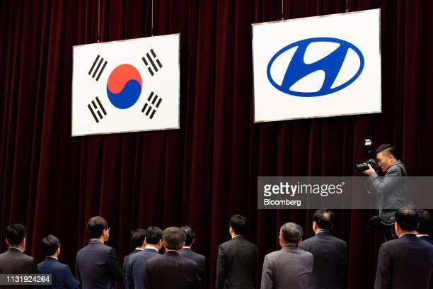 Executives of Hyundai Motor Co stand under the flags of South Korea left and Hyundai Motor during the company's annual shareholders meeting in Seoul...