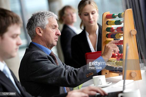 Executives on laptops, older man with abacus