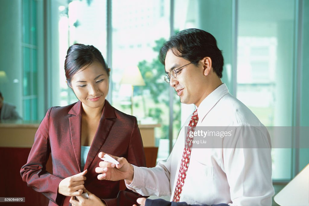 Executives Reading Business Card Stock Photo | Getty Images